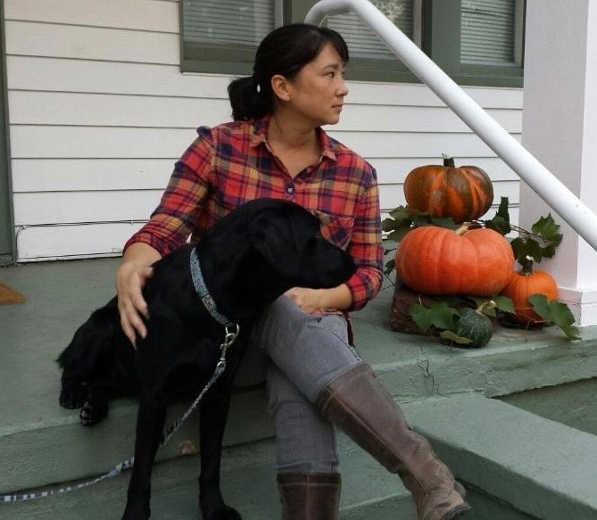 photo of a female student in a red plain shirt with a black dog