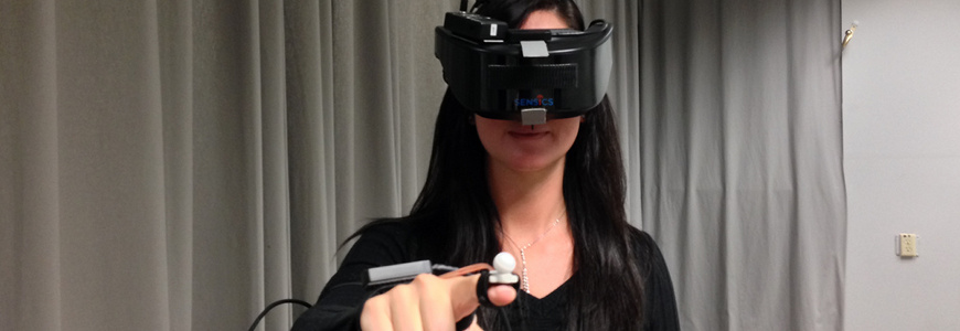 young woman in virtual reality gear pointing towards camera