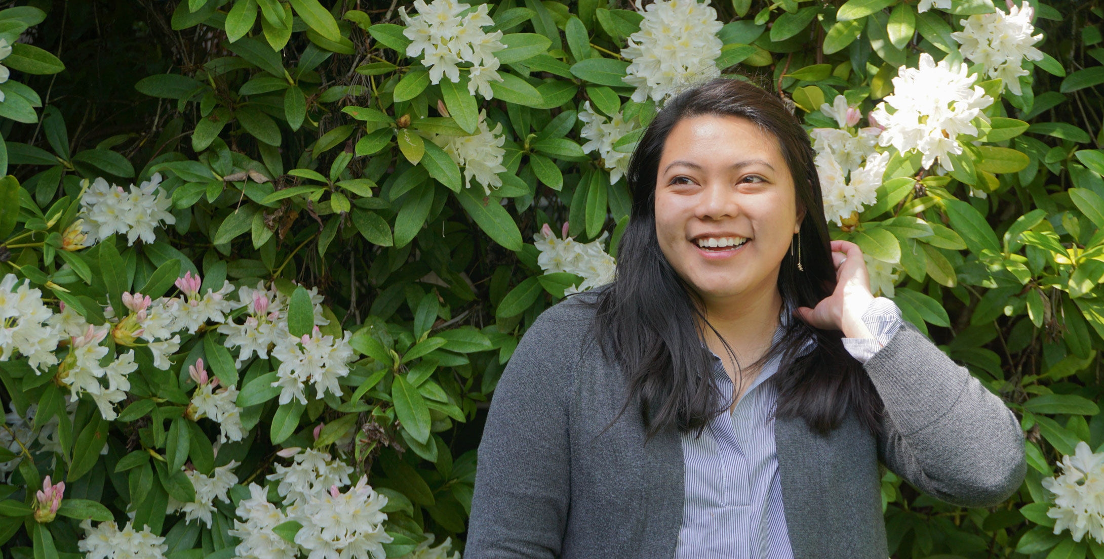 Photo of Sydney Phu in front of flower bush