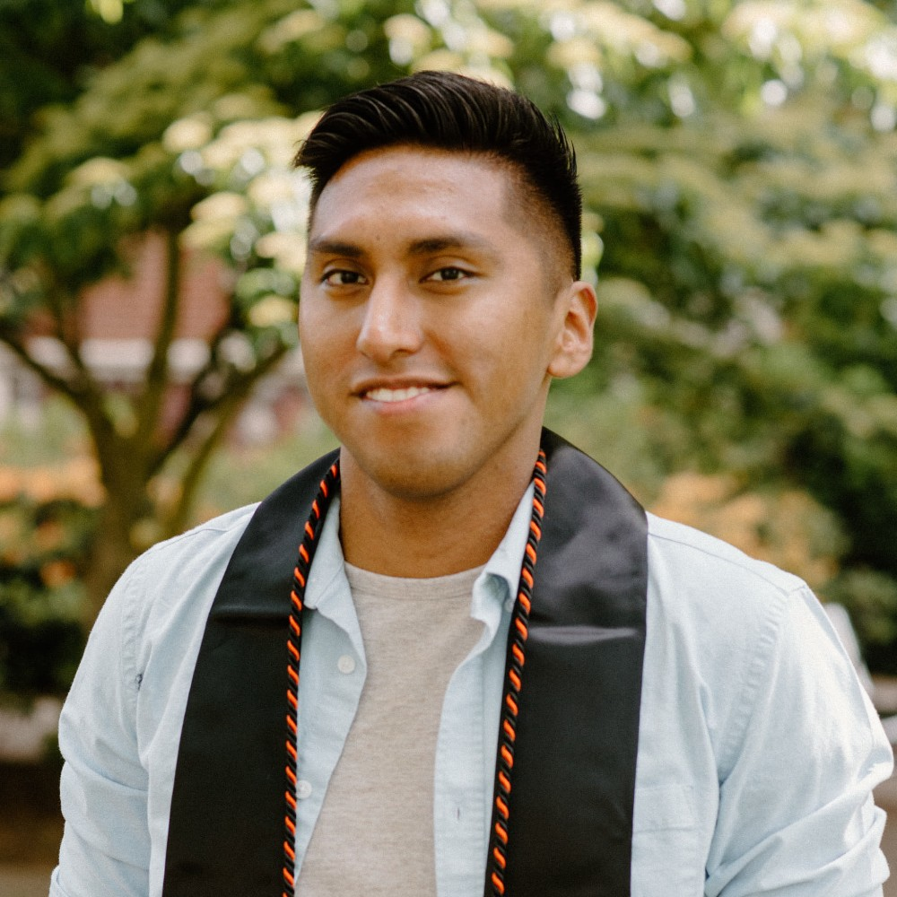 photo of a young man in a blue button down wearing a graduation stole from Oregon State University
