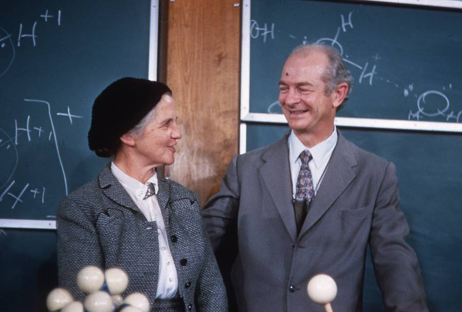 ava and linus pauling standing in front of a blackboard talking with each other