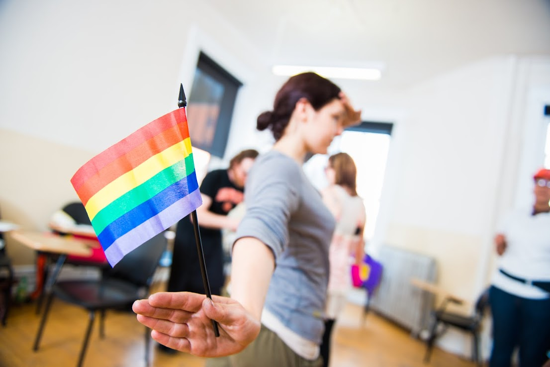 A person, facing away from the viewer, holds a small rainbow flag in their right hand. Their left hand is at their forehead like a military salute.