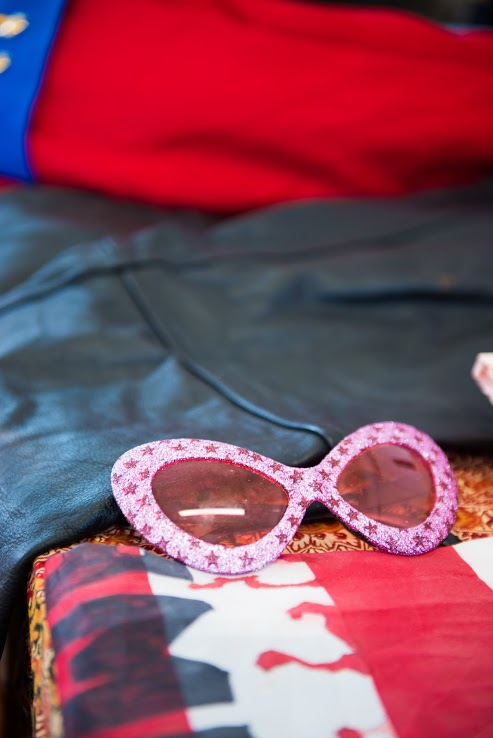 Close up of a photograph of pink, gliterry sunglasses.
