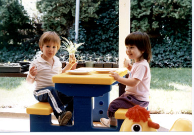 two small children sitting at a little table