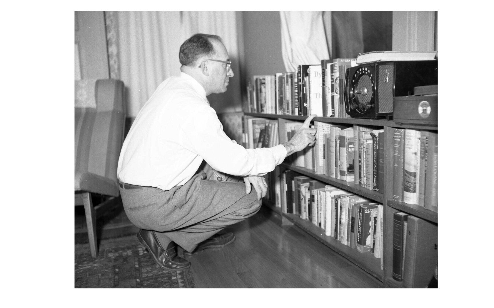 Bernard Malamud kneeling at bookshelf