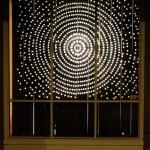 dots of light arranged in a radial pattern seen threw a window