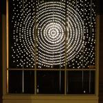dots of light arranged in a radial pattern seen threw a window