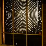 angular view of dots of light arranged in a radial pattern seen threw a window