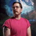 transexual person with mustache in T-shirt and glasses looking away with forest and mountain backround