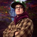 transexual person wearing plaid coat, glasses, and baseball hat looking away with waterfall backround