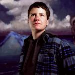 transexual person wearing plaid coat looking away with mountain and sky backround