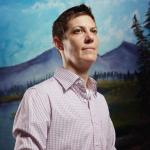 transexual person wearing button up shirt looking away with lake, mountain, sky backround