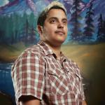 transexual person with plaid shirt looking away with mountain forest backround