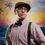 transexual person wearing suspenders, bow tie, and hat looking away with tropical ocean backround