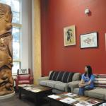 woman sitting on a couch and looking at a large totem pole inside the native american longhouse