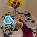 Illuminated coffee cup with flowers, cereal, and newspaper on top of a table