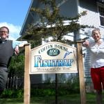 Man and woman standing by fishtrap sign